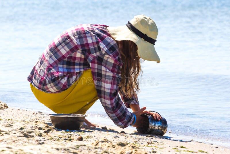 Młoda dziewczyna w kapeluszu od słońca obsiadania na jego haunches i obmyć dęciaka skala łasowaniu kulinarny zioło obraz royalty free