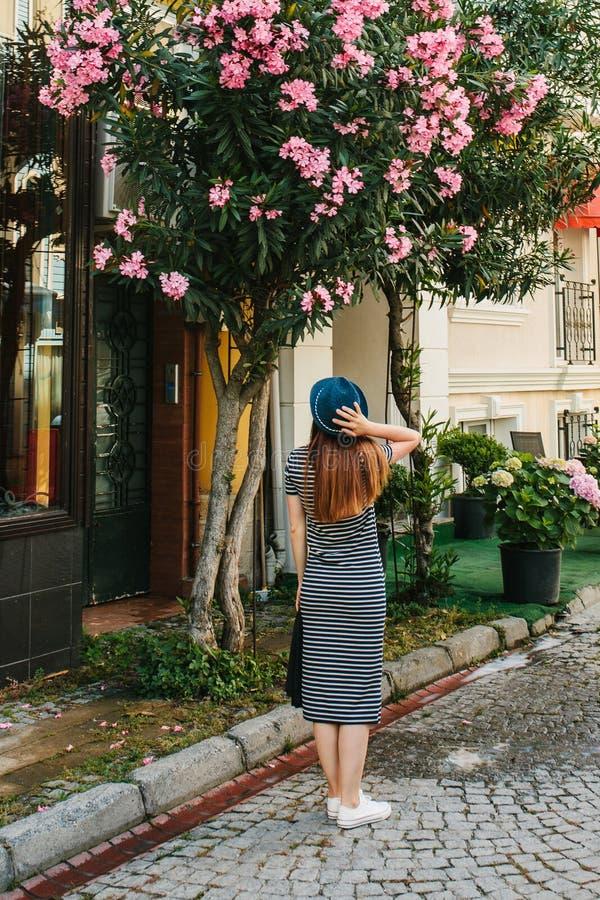 Młoda dziewczyna w kapeluszu podziwia pięknych kwiaty obok domu fotografia stock