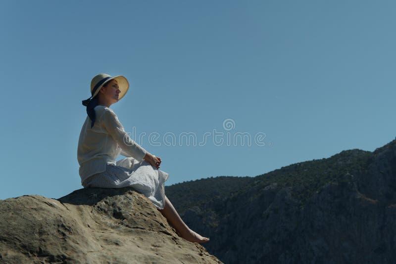 Młoda dziewczyna w kapeluszu siedzi na wysokim kamiennym wzgórzu cieszy się piękną naturę przeciw tłu wzgórza na pogodnym letnim  zdjęcie stock