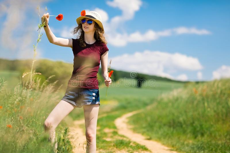 M?oda dziewczyna w kapeluszu skuba maczka kwiaty - fury drog? zdjęcie stock