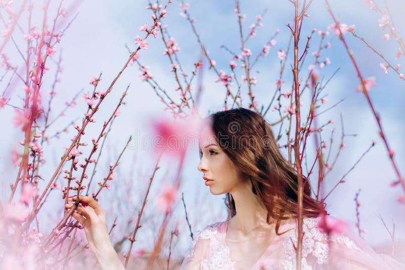 Młoda dziewczyna w menchia kwitnącym ogródzie brzoskwinie w różowi suknię i makeup obrazy royalty free