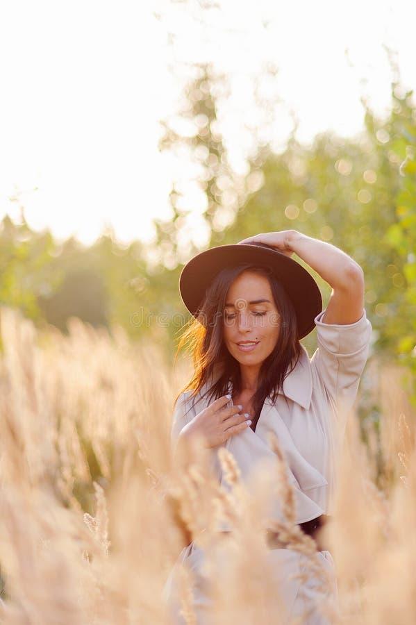 Młoda dziewczyna w pszenicznym polu w czarnym kapeluszu zdjęcia royalty free