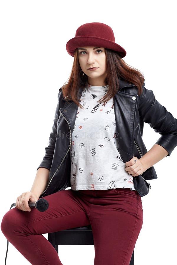 Młoda dziewczyna w rzemiennej modnej kurtce i czerwień kapeluszowy śpiew z microp obraz stock