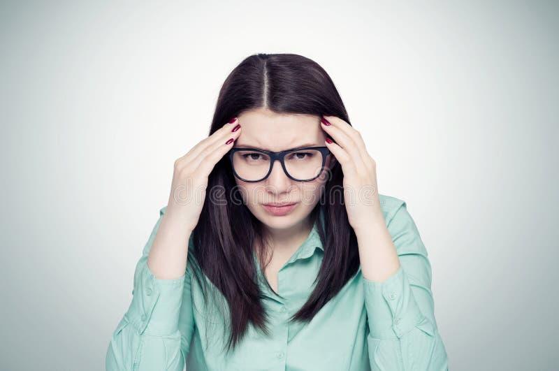 Młoda dziewczyna w szkłach trzyma jej głowę, migreny pojęcie fotografia stock