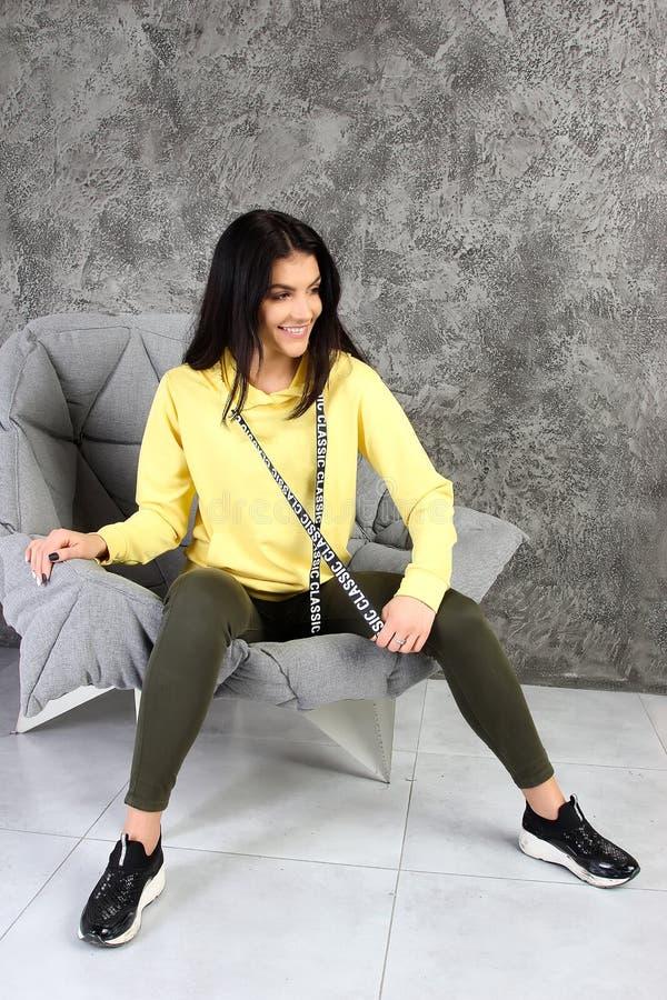 Młoda dziewczyna w tracksuit siedzi w eleganckim wnętrzu zdjęcia stock