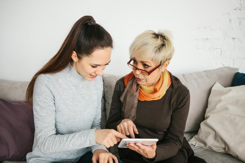 Młoda dziewczyna wyjaśnia starsza kobieta, pokazuje niektóre zastosowanie lub uczy ci dlaczego używać a dlaczego używać pastylkę zdjęcia stock