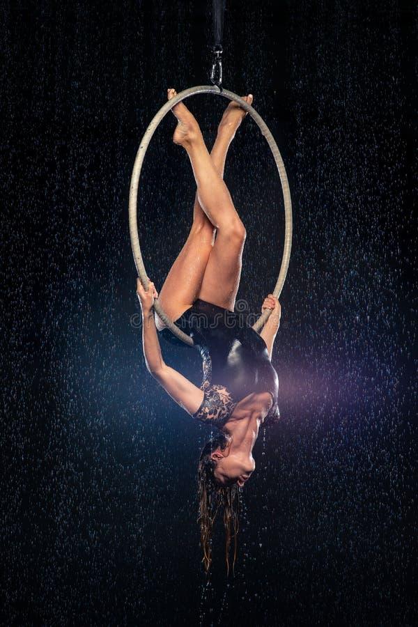 Młoda dziewczyna wykonuje akrobatycznych elementy w antena pierścionku Aqua Pracowniani mknący występy na czarnym tle zdjęcie stock