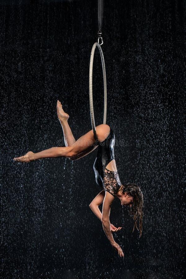 Młoda dziewczyna wykonuje akrobatycznych elementy w antena pierścionku Aqua Pracowniani mknący występy na czarnym tle obrazy stock