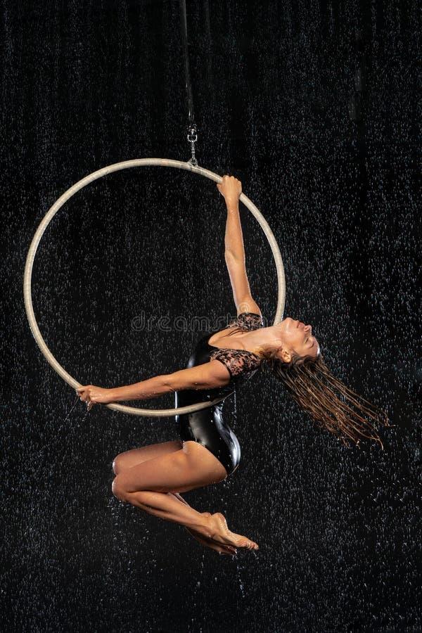 Młoda dziewczyna wykonuje akrobatycznych elementy w antena pierścionku Aqua Pracowniani mknący występy na czarnym tle obrazy royalty free