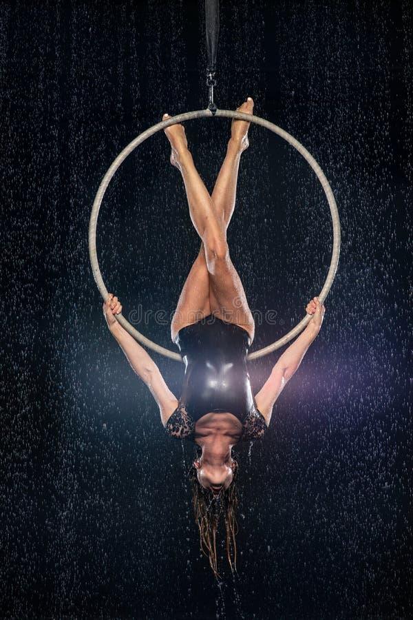 Młoda dziewczyna wykonuje akrobatycznych elementy w powietrznym obręczu Czarny Aqua studio zdjęcia royalty free