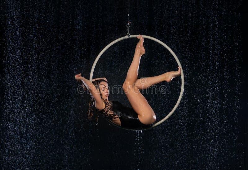 Młoda dziewczyna wykonuje akrobatycznych elementy w powietrznym obręczu Czarny Aqua studio obrazy stock