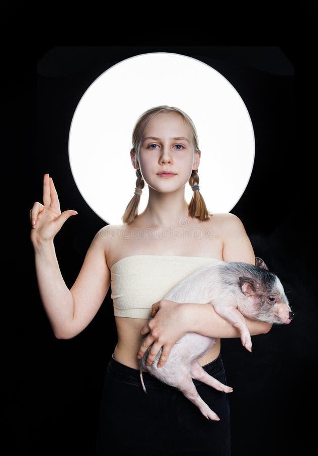 Młoda dziewczyna z świnią na czarnym tle, kreatywnie portret obrazy royalty free
