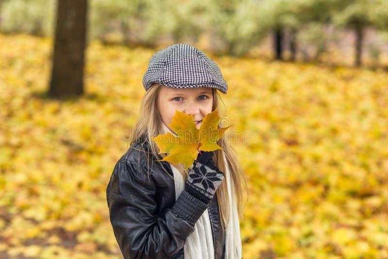 Młoda dziewczyna z żółtym liściem w jesień parku zdjęcie stock
