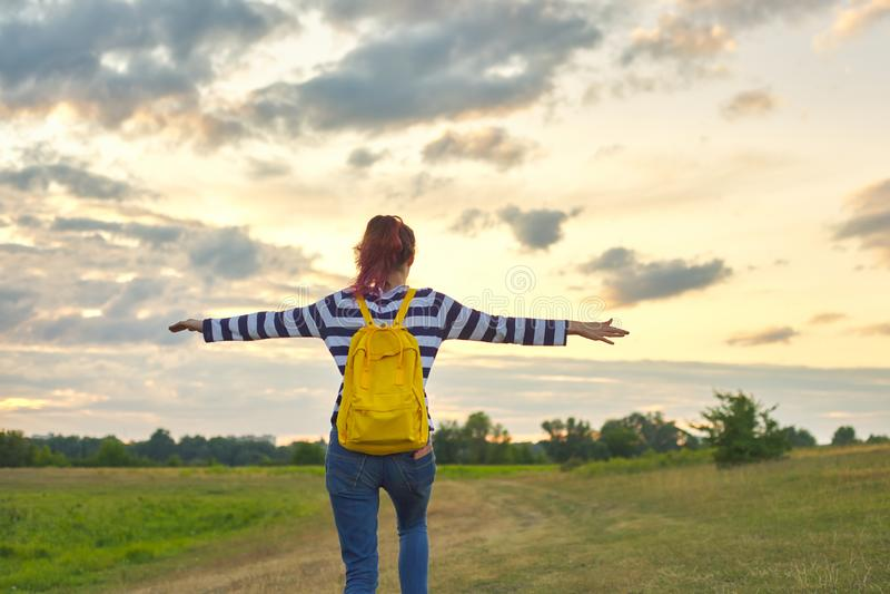 Młoda dziewczyna z żółtym plecakiem, ona z powrotem z otwartymi rękami obraz stock