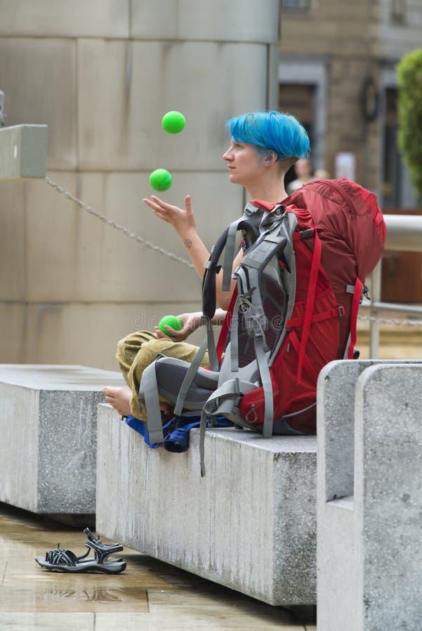 Młoda dziewczyna z błękitnymi włosy żonglerkami z gumowymi piłkami fotografia stock