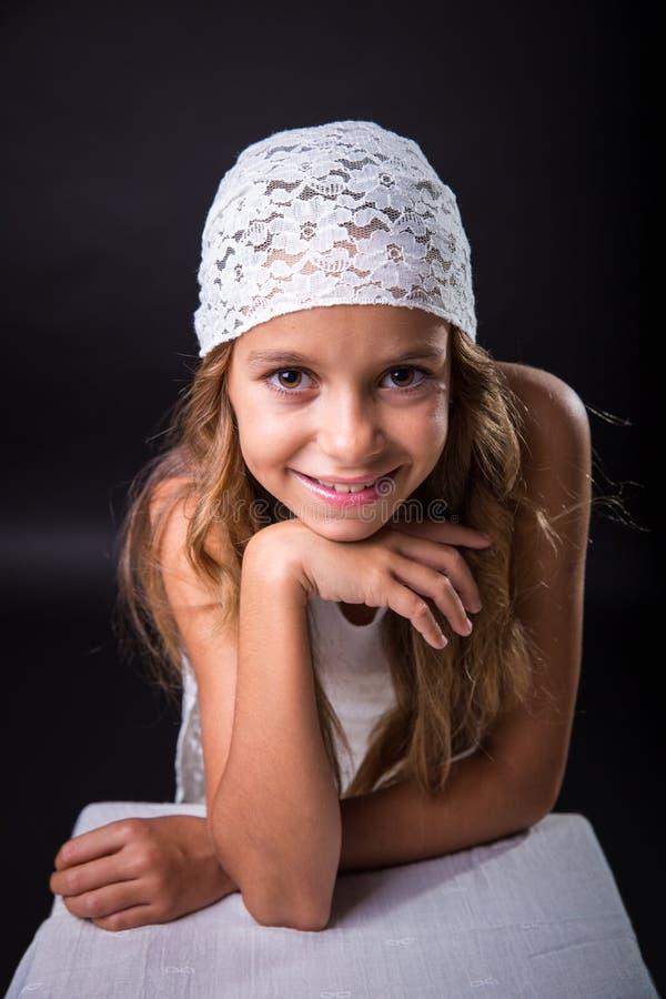 Młoda dziewczyna z biały nakrętki ono uśmiecha się zdjęcia royalty free