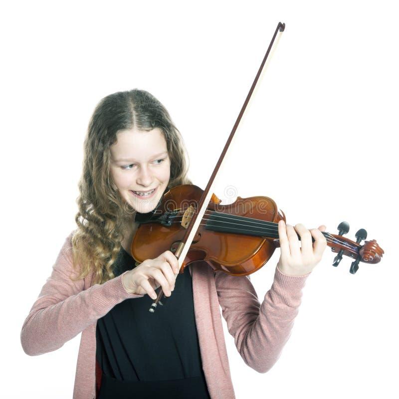 Młoda dziewczyna z blond kędzierzawym włosy bawić się skrzypce w studiu obrazy stock