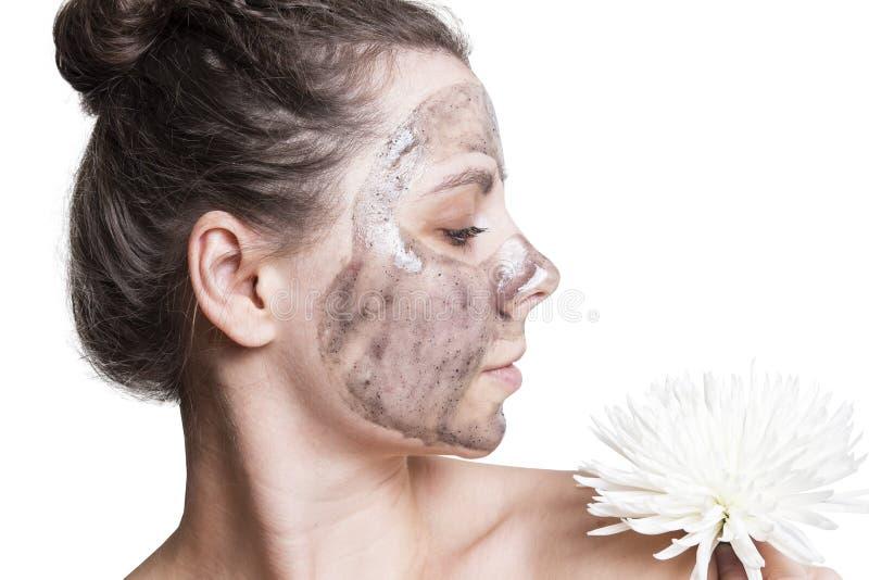Młoda dziewczyna z czarną twarzową maską dla twarzy opieki odizolowywającej na białym tle Skincare pojęcie obraz royalty free