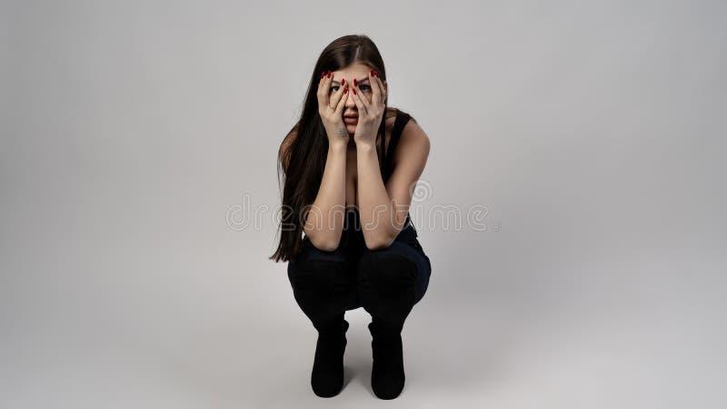 Młoda dziewczyna z czarni włosy pozuje na czarnym tle obraz stock