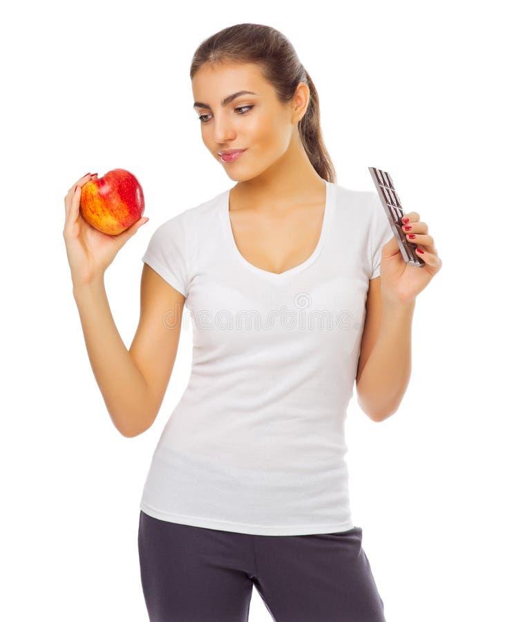 Młoda dziewczyna z czerwonym jabłkiem i czekoladą obraz stock