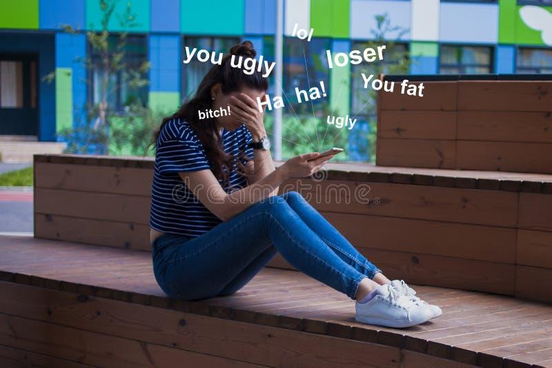 Młoda dziewczyna z długie włosy, z telefonem, płacz, zakrywający twarz z ręką, siedzi z nogami na drewnianym schodki obrazy stock
