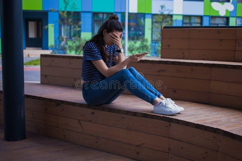 Młoda dziewczyna z długie włosy, z telefonem, płacz, zakrywający twarz z ręką, siedzi z nogami na drewnianym schodki fotografia royalty free