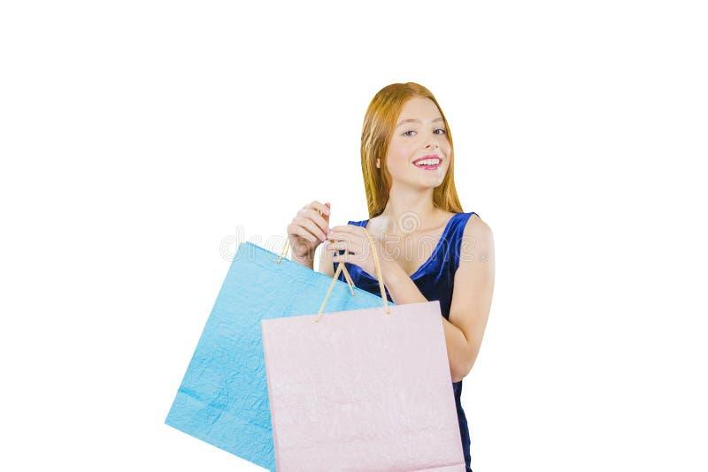 Młoda dziewczyna z długimi czerwonymi włosianymi mienia dwa torbami z nowymi zakupami i patrzeć strona z jego głową patrzeje zdjęcie royalty free