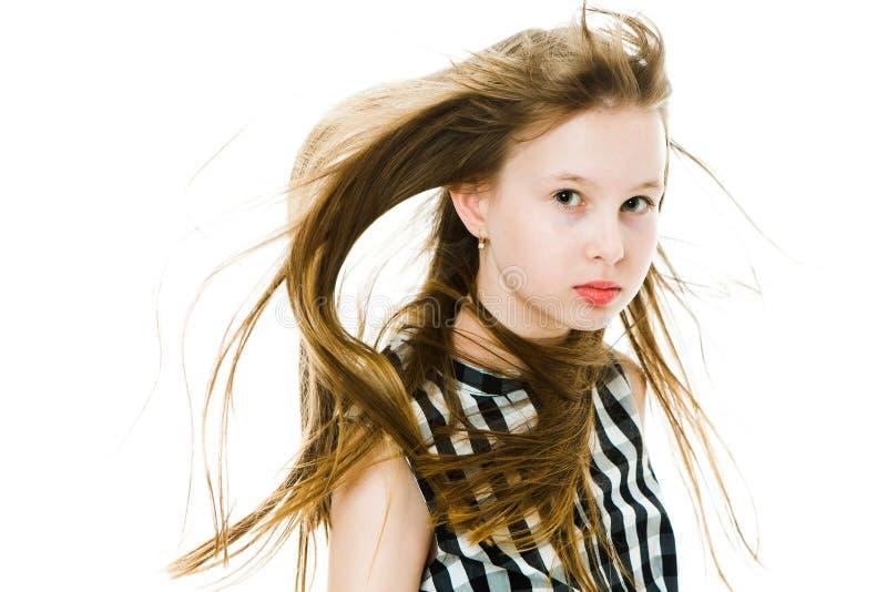 Młoda dziewczyna z długimi prostymi włosami dmuchającymi wiatrem w studiu fotografia royalty free
