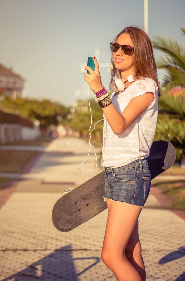 Młoda dziewczyna z deskorolka i hełmofonów patrzeć zdjęcia stock