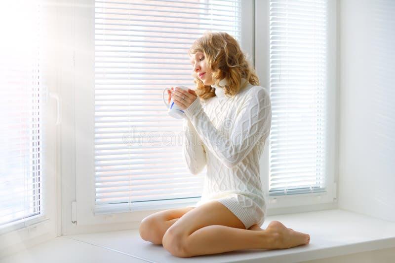 Młoda dziewczyna z filiżanką herbata zdjęcie stock