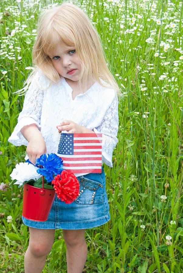 Młoda dziewczyna z goździkami i flaga fotografia stock