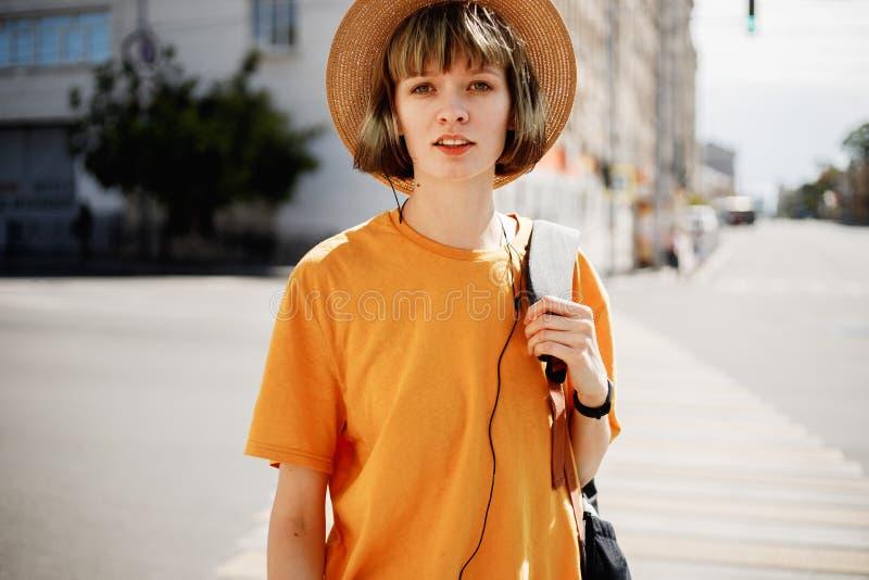 Młoda dziewczyna z hełmofonami w żółtej koszulce i słomianym kapeluszu chodzi z plecakiem wzdłuż miasto ulicy na lecie zdjęcie royalty free