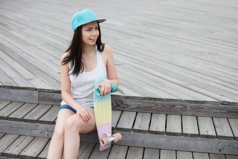 Młoda dziewczyna z krótkim krążownika deskorolka pokładem outdoors zdjęcie stock
