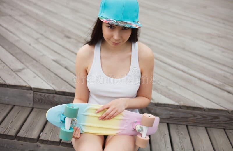 Młoda dziewczyna z krótkim krążownika deskorolka pokładem outdoors fotografia royalty free