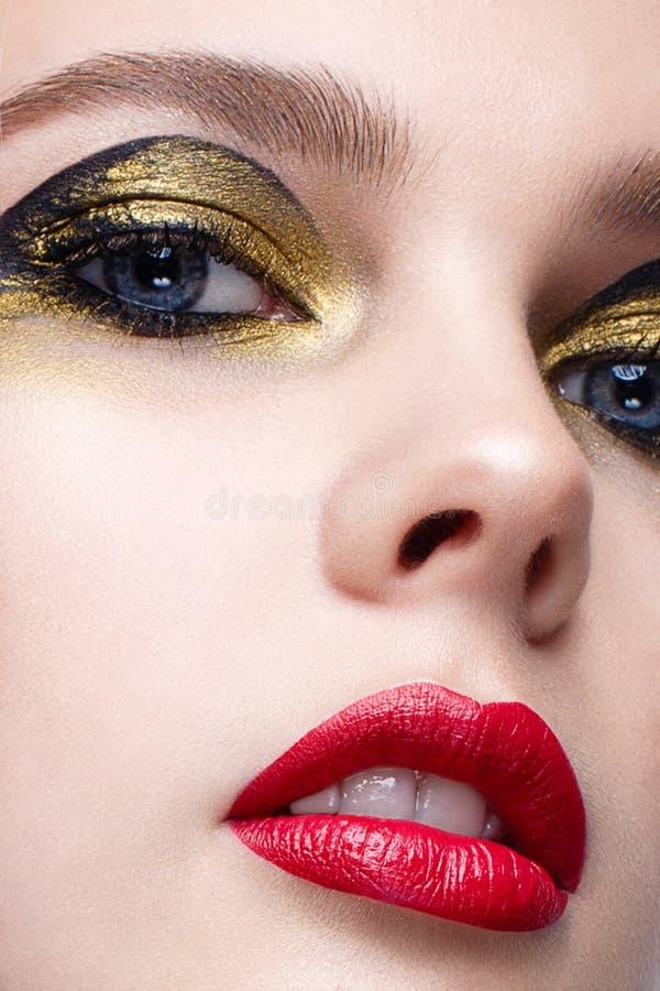 Młoda dziewczyna z kreatywnie czarnym i złocistym makeup Piękny model z checker na czerwieni wargach i szyi idealna skóra Piękno  zdjęcia royalty free