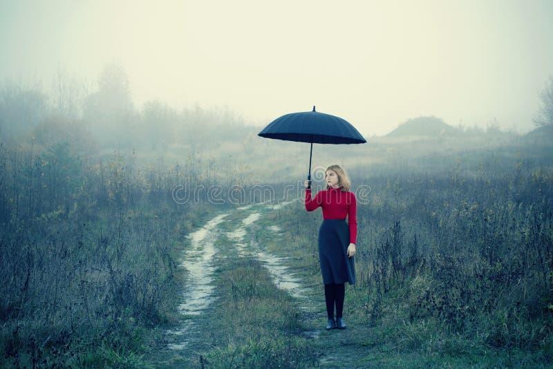 Młoda dziewczyna z parasolem w jesieni polu fotografia stock