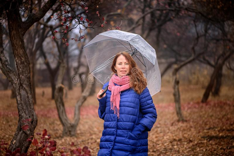 Młoda dziewczyna z parasolem w parkowym jesień dniu zdjęcie royalty free