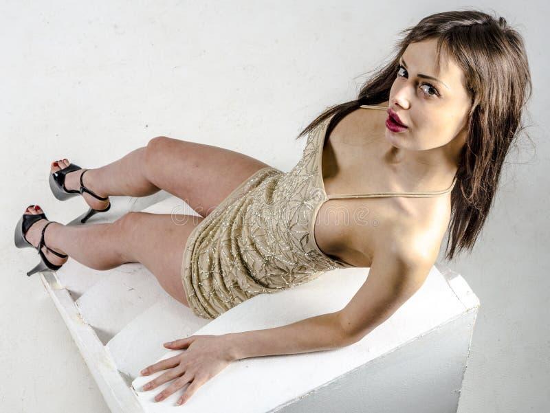 Młoda dziewczyna z piękną postacią w modnej złotej sukni w ciasnej minispódniczce, szpilki i platforma fotografia stock