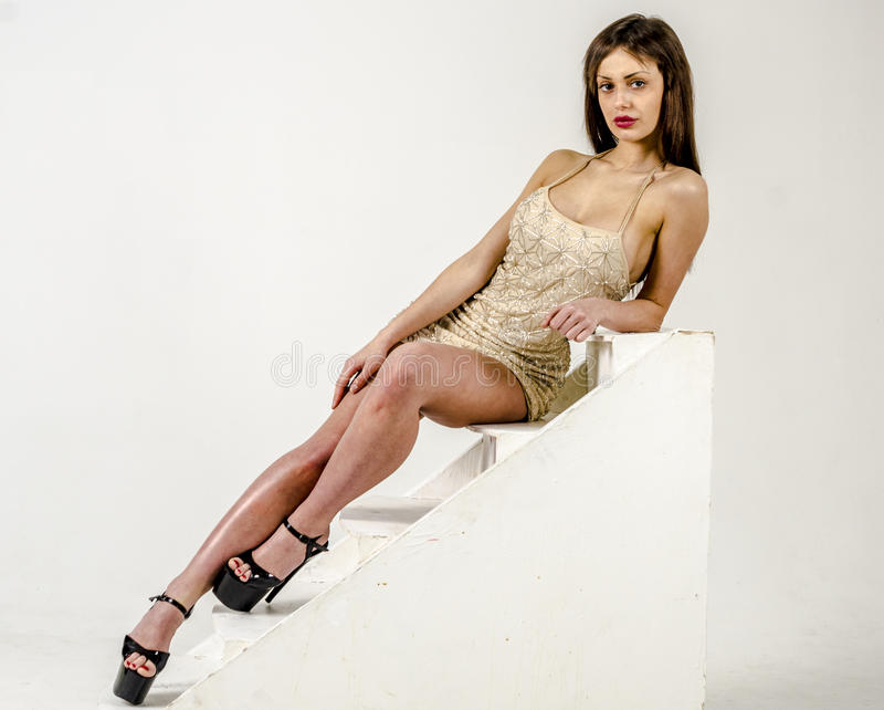 Młoda dziewczyna z piękną postacią w modnej złotej sukni wewnątrz, czarna platforma i szpilki i ubierał dla pa zdjęcia stock
