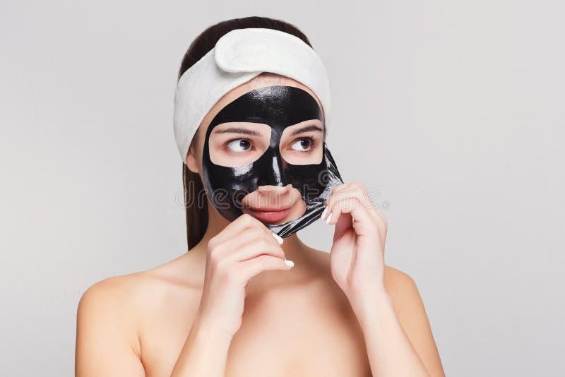 Młoda dziewczyna z purifying czarnej twarzy maskę obrazy stock