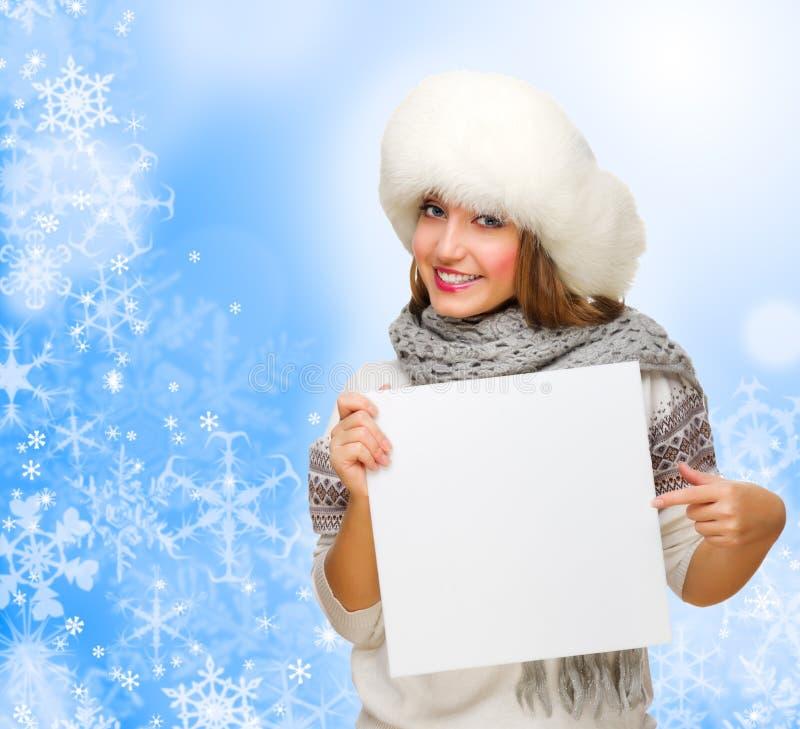 Młoda dziewczyna z pustą kartą na zimy tle fotografia royalty free