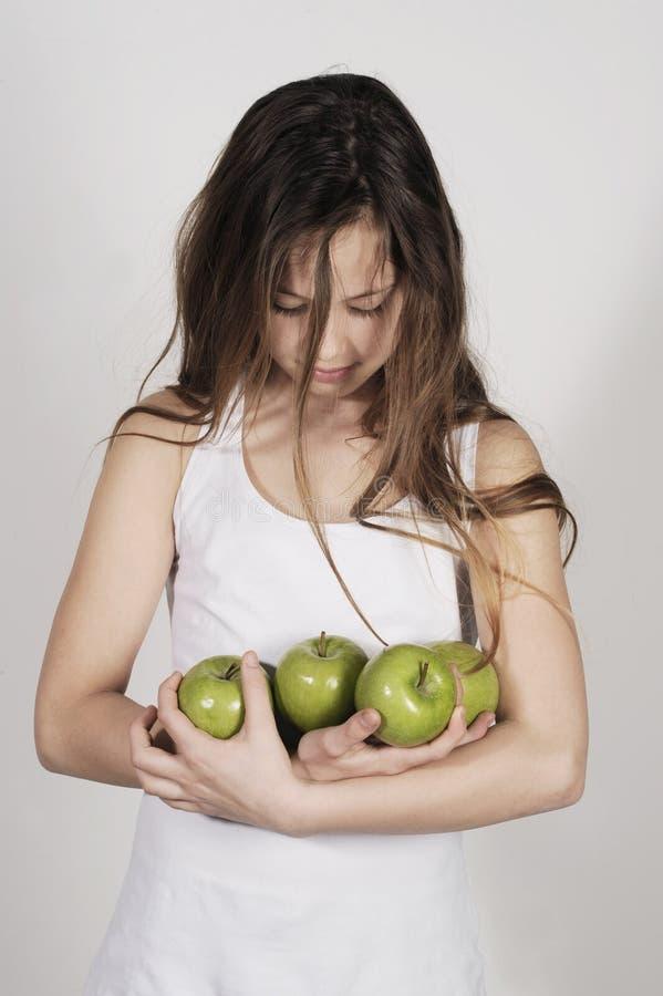 Młoda dziewczyna z stosem jabłka zdjęcia stock