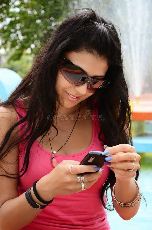 Młoda dziewczyna z telefon komórkowy w th parku zdjęcia stock