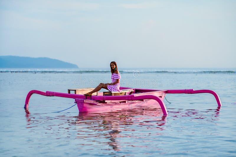 Młoda dziewczyna z uśmiechem cieszy się zmierzch w dennym obsiadaniu na różowej łodzi obrazy stock