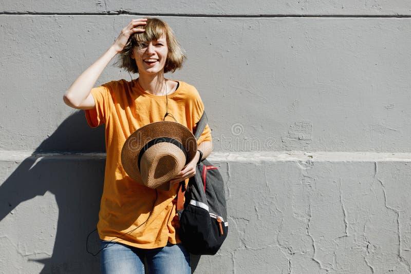 Młoda dziewczyna z ubiera w żółtej koszulce trzyma słomianego kapelusz w jej ręka stojakach opiera na szarym budynku w mieście zdjęcie stock