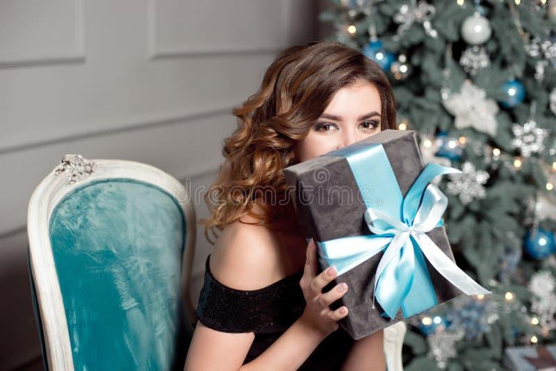 Młoda dziewczyna z wspaniałym falistym włosy, jaskrawy makeup, chwyty w jej rękach zawijający prezent, siedzi w barwiącym krześle obrazy royalty free