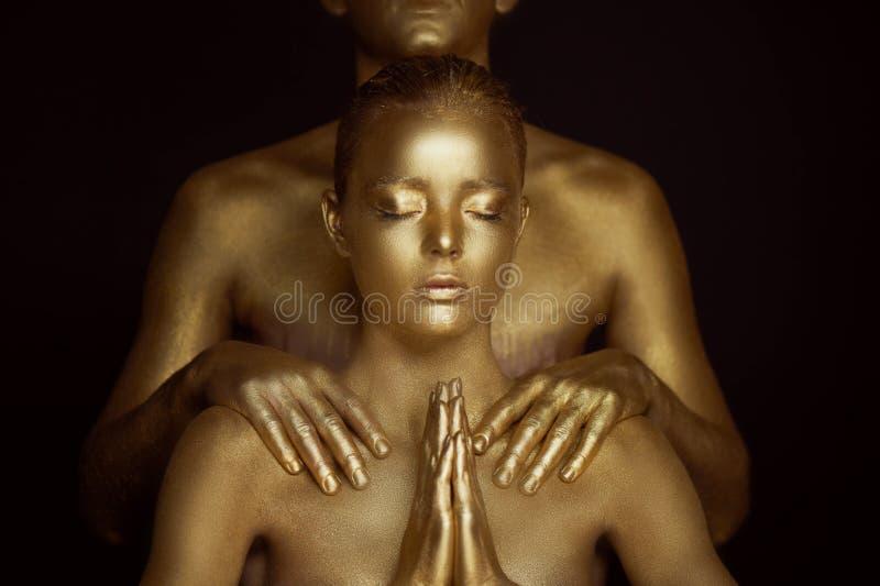 Młoda dziewczyna, zakrywająca w złocistej farbie Ręki spinają w Buddyjskiej modlitwie Suplika, prośba Na ramionach obraz stock