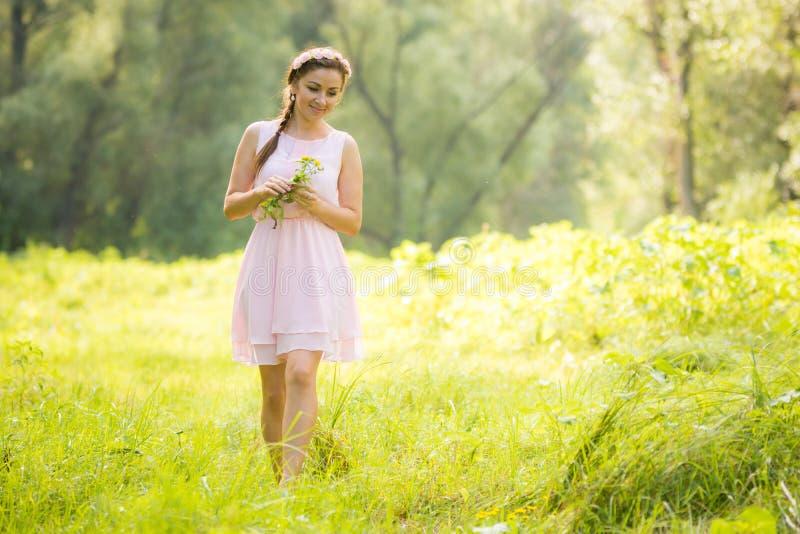 Młoda dziewczyna zbiera dzikich kwiaty w lata światła sukni fotografia stock