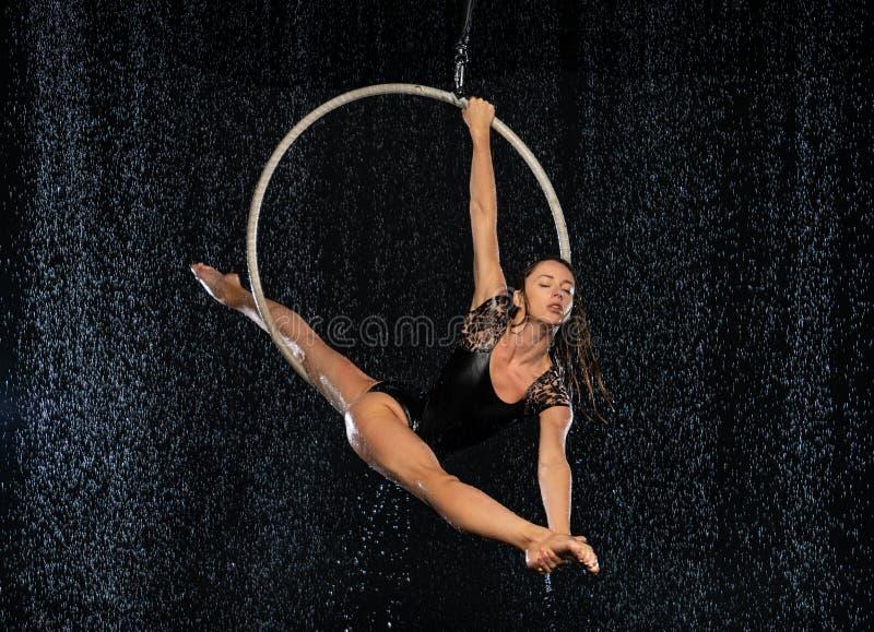 Młoda elastyczna dziewczyna wykonuje rozłamy w antena pierścionku Aqua Pracowniani mknący występy na czarnym tle zdjęcie royalty free