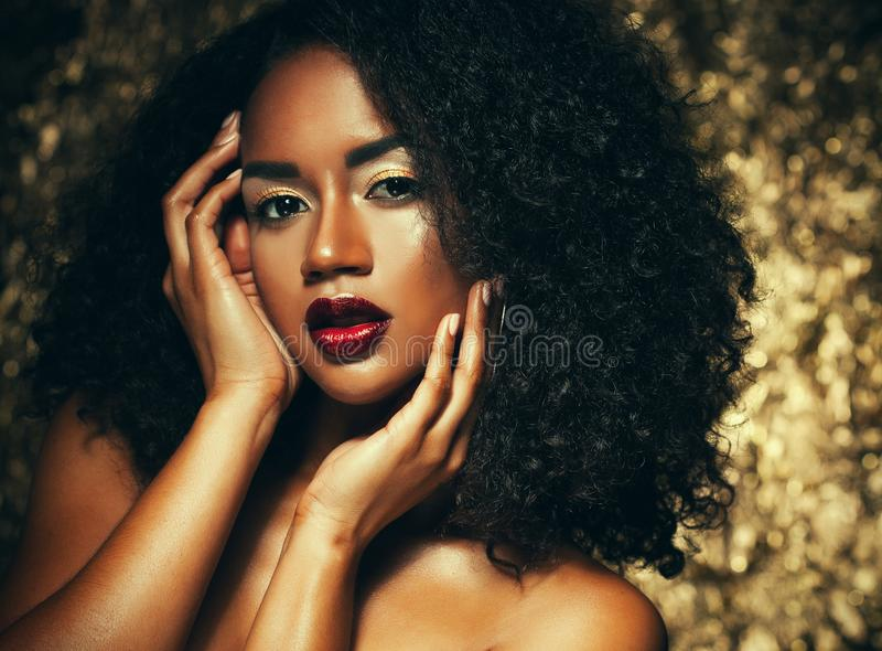 Młoda elegancka amerykanin afrykańskiego pochodzenia kobieta z afro włosy Splendoru makeup złoty tło zdjęcie stock